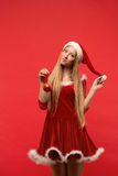 Santa girl posing on a red background with the toy. Royalty Free Stock Photo
