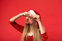 Santa girl posing on a red background with the toy. Royalty Free Stock Photos