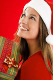 Santa Girl with present. Portrait of a smiling and dreaming Santa Girl with present Stock Photos