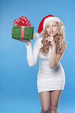Santa girl with a present gifts saying shh Royalty Free Stock Photography