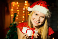 Santa girl with present near the Christmas tree Stock Photo