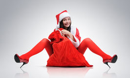 Santa Girl with a red bag of gifts. On background Royalty Free Stock Image
