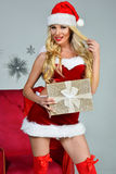 Santa-girl in red dress and hat holding  present. Royalty Free Stock Photos