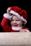 Santa Girl Removing Hat. Pretty little girl dressed in a Santa-style dress and hat; looking over the arm of a couch while removing her hat and smiling happily Royalty Free Stock Photo