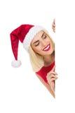 Santa Girl rubia detrás de un cartel Foto de archivo