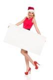 Santa Girl rubia que presenta con el cartel blanco Foto de archivo