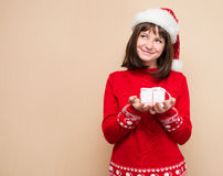 Santa girl in santa hat with Christmas gift in her hand dreaming Stock Image