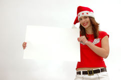 Santa girl with sign. A beautiful caucasian white teenage girl with happy smiling facial expression dressed as Santa Claus and holding a white blank cardboard Stock Photography