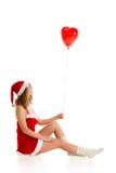 Santa girl sitting and looking at heart shaped balloon Stock Photos
