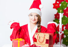 Santa girl sitting on the table with gift boxes Stock Image