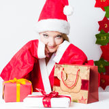 Santa girl sitting on the table with gift boxes Stock Photo