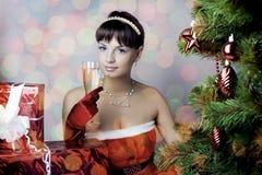 Santa girl sitting under the tree Stock Images