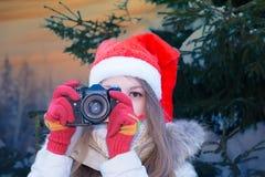 Santa girl with SLR camera. Cute teenage girl in Santa hat looking through SLR camera Stock Photos