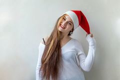 Christmas woman with Santa hat. Santa girl smiling in red Santa hat. Christmas Santa hat  woman portrait . Smiling happy girl on white background Royalty Free Stock Photos