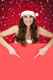 Santa girl on snow  pointing at sign Royalty Free Stock Photography