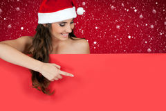 Santa girl in snow pointing to billboard Stock Image