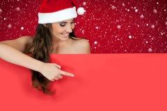 Santa girl in snow pointing to billboard. Smiling santa girl pointing on red billboard while snowing Stock Image