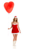 Santa girl standing with heart shaped balloon Stock Photos