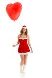 Santa girl standing with heart shaped balloon Stock Photos