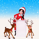 Santa girl is standing with sign and reindeer Stock Photos