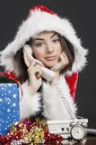 Santa girl talking on telephone. Portrait of gorgeous Santa girl speaking on a telephone over dark background. Alarm clock, gift box and decorations on table Royalty Free Stock Photos