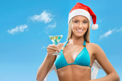 Santa girl wearing Christmas hat. On sky background Royalty Free Stock Photo