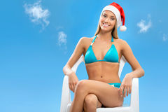 Santa girl wearing Christmas hat. On sky background Stock Photos