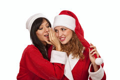 Santa girl whispering to her girlfriend ear Stock Photography