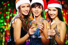 Santa girls. Pretty girls in Santa caps toasting at Christmas party and looking at camera with smiles stock photo