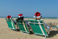 Santa girls on a sunny beach. 3 women wearing santa hat relaxing on a sunny beach waiting for christmas looking at the blue ocean royalty free stock photo