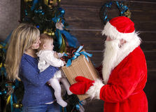 Santa gives a gift to mum with baby Stock Photo