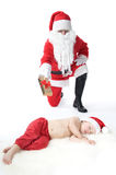 Santa is giving gift to sleeping baby Stock Image
