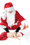 Santa is giving gift to sleeping baby Royalty Free Stock Image