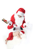 Santa is giving gift to sleeping baby Stock Photography
