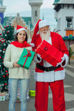 Santa giving a gift to a young woman Royalty Free Stock Images