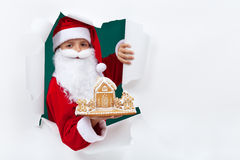 Santa giving you a gingerbread cookie house Royalty Free Stock Photography