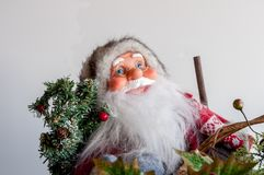 Santa with glasses. Santa Claus figure wearing glasses carrying festive branch or Christmas tree. Close up Royalty Free Stock Photo