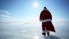 Santa Goes Into the Distance. Santa Claus walks dancing on Lake Baikal stock video