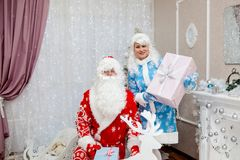 Santa and granddaughter Snow Maiden with gifts in the new year in a festive interior. New Year`s and Christmas Royalty Free Stock Photos