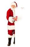 Santa: Guardando o presente de Natal pelo cartão branco Fotografia de Stock