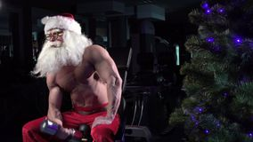 Santa in a gym training biceps 002 stock video footage