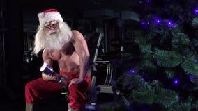 Santa in a gym training biceps 006 stock footage