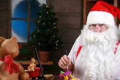 Santa hace los juguetes en su taller Imagen de archivo libre de regalías
