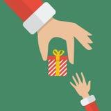 Santa hand giving a gift box to kid Royalty Free Stock Image