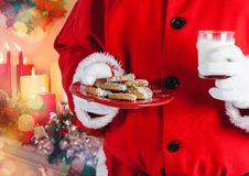 Santa hand holding cookies and a glass of milk. Digitally generated christmas background Stock Photography