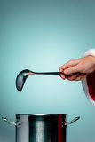 The Santa hand holding a ladle or kitchen spoon Royalty Free Stock Photos