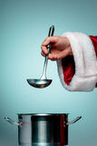 The Santa hand holding a ladle or kitchen spoon Stock Photo