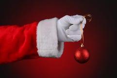 Santa hand som rymmer den röda prydnaden Fotografering för Bildbyråer
