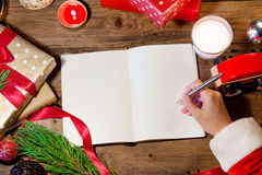 Santa hand writing on christmas book. Santa hand writing on christmas book Royalty Free Stock Photo