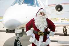Santa With Hands On Hip Against Private Jet. Portrait of Santa with hands on hip against private jet at airport terminal Stock Photography